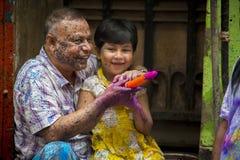 Um pai e um momento alegre das crianças do holi o festival das cores na feira de Shakhari, Dhaka, Bangladesh Imagem de Stock Royalty Free