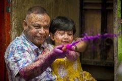 Um pai e um momento alegre das crianças do holi o festival das cores na feira de Shakhari, Dhaka, Bangladesh Imagens de Stock Royalty Free