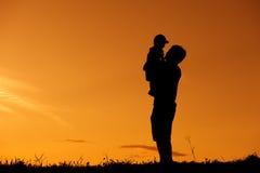 Um pai e um filho que jogam fora no por do sol fotos de stock