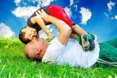 Um pai e um rapaz pequeno que colocam na grama Imagens de Stock Royalty Free