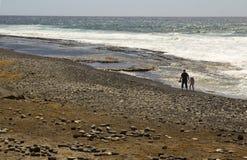 Um pai e uma criança relaxam e jogam junto no Pebble Beach em Playa Las Americas em Teneriffe nas Ilhas Canárias espanholas imagens de stock