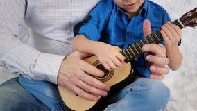 Um pai ensina seu filho jogar a guitarra Um rapaz pequeno toca nas cordas de uma guitarra das crianças pequenas com o seu vídeos de arquivo