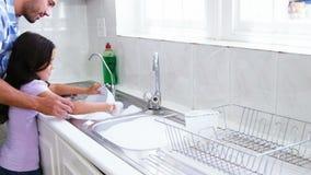Um pai está ensinando sua filha lavar os pratos filme