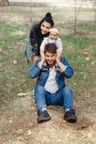 Um pai feliz est? sentando-se em um gramado, uma filha est? em seus ombros, uma m?e est? abra?ando uma fam?lia, um dia bonito do  foto de stock royalty free