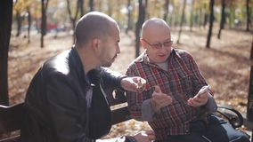 Um pai idoso e seu filho adulto que sentam-se em um café e em uma fala bebendo do banco de parque Filho adulto de um pai idoso video estoque