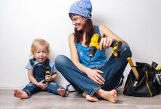 Um pai: A mamã executa os trabalhos domésticos dos homens com uma filha pequena e sentou-se para baixo para descansar na parede b imagem de stock royalty free