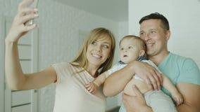 Um pai novo dos pares faz um selfie junto com seu bebê Em sua casa brilhante nova Conceito - festa de inauguração, feliz filme