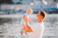 Um pai novo guarda um ano de seu filho em seus braços com um sorriso e ama abraços e joga-o no banco de rio na praia Foto de Stock