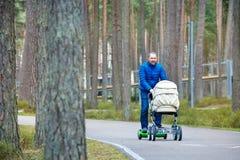Um pai novo na placa do 'trotinette' do giroscópio com um carrinho de criança anda através do parque do outono imagem de stock
