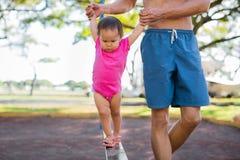 Um pai que ajuda sua caminhada da criança, equilibrando em um obstáculo do campo de jogos fotos de stock