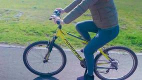 Um paizinho entusiasmado ajuda sua filha asiática nova a montar pela primeira vez sua bicicleta cor-de-rosa sem rodas de treiname filme