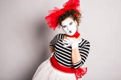 Um palhaço da mulher mimica o levantamento no estúdio, conceito do dia dos enganados Fotos de Stock