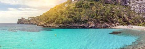 Um panorama de águas azuis claras e de uma praia em um vale da montanha Imagem de Stock Royalty Free