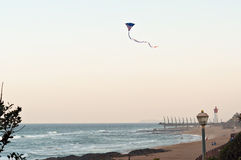 Um papagaio da bandeira americana voa sobre a praia em rochas de Umhlanga, com o cais do milênio e o farol no fundo Imagens de Stock Royalty Free