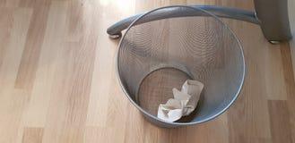 Um papel dobrado no escaninho de lixo cinzento transparente do metal imagem de stock