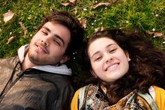 Um par adolescentes que encontram-se na grama Foto de Stock