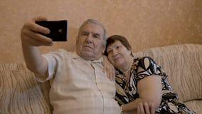 Um par adulto faz o selfie Estão sentando-se em casa no sofá Use um smartphone para fotos filme