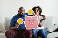 Um par africano que guarda o conceito home do investimento da economia da família dos ícones do dinheiro da economia Imagem de Stock Royalty Free