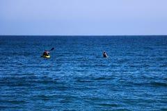 Um par amigos que canoeing em uma canoa de madeira em um dia ensolarado EUA fotografia de stock royalty free
