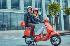 Um par atrativo, um homem considerável e montada fêmea 'sexy' junto em um 'trotinette' retro vermelho em uma cidade foto de stock royalty free
