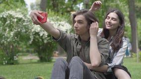 Um par bonito de estudantes que tomam o selfie que senta-se na grama no parque O indiv?duo est? no primeiro plano, o aperto da me vídeos de arquivo