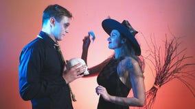 Um par bonito, um homem e uma mulher na bruxa e nos trajes do zombi para Dia das Bruxas, 4k, lento-movimento, guardam o crânio de video estoque