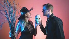 Um par bonito, um homem e uma mulher na bruxa e nos trajes do zombi para Dia das Bruxas, 4k, lento-movimento, guardam o crânio de vídeos de arquivo