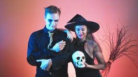Um par bonito, um homem e uma mulher na bruxa e nos trajes do zombi para Dia das Bruxas, 4k, tiro do lento-movimento, guardam um  video estoque