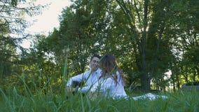 Um par bonito na roupa branca está sentando-se na grama verde Data, ternura e amor românticos video estoque