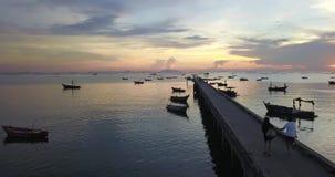Um par bonito que anda na ponte do molhe pelo mar com por do sol, tiro do zangão, videografia aérea video estoque