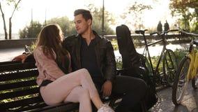 Um par caucasiano bonito para sentar o abraço em um banco de parque Retrato de um par no amor em um banco no parque e vídeos de arquivo