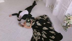 Um par com composição em sua mentira da cara no assoalho em uma sala do vintage Halloween vídeos de arquivo