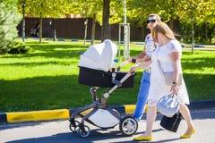 Um par com uma criança em uma cadeira de rodas está na estrada imagem de stock