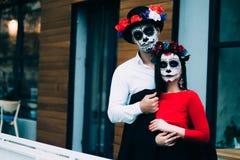 Um par, crânio vestindo para compensar Todo o dia de almas Composição do crânio do açúcar do menino e da menina pintado para a po imagem de stock