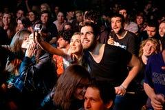 Um par da multidão toma um selfie com uma câmera de Gopro na fase do biquini Imagem de Stock Royalty Free
