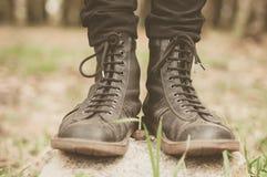 Um par das botas de couro na floresta Fotografia de Stock