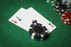 Um par de áss com uma pilha de microplaquetas de pôquer fotografia de stock