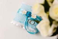 Um par de alianças de casamento em um descanso azul fotografia de stock