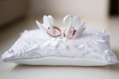 Um par de alianças de casamento em um descanso branco imagens de stock royalty free