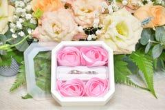 Um par de alianças de casamento em uma caixa cercada por muitas flores foto de stock royalty free