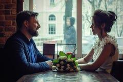 Um par de amantes está sentando-se em um café foto de stock