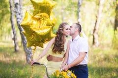 Um par de amor em uma caminhada no verão ou na mola na natureza com uma bicicleta e os balões sob a forma das estrelas douradas O imagens de stock royalty free