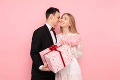 Um par de amor, um homem dá a uma mulher um ramalhete das tulipas e de uma caixa com um presente em um fundo cor-de-rosa Conceito imagem de stock