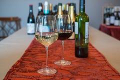 Um par de copos de vinho e de garrafas do vinho Fotos de Stock Royalty Free