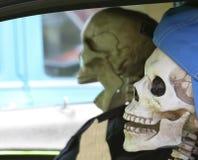 Um par de esqueletos adolescentes que sentam-se no tráfego Imagens de Stock Royalty Free