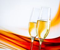 Um par de flautas de champanhe com bolhas douradas no borrão ilumina o fundo Fotos de Stock