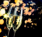 Um par de flautas de champanhe com bolhas douradas no fundo claro dourado e escuro Foto de Stock Royalty Free