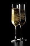 Um par de flautas do champanhe com bolhas douradas no fundo de madeira preto Fotos de Stock Royalty Free