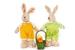 Um par de lebres macias do brinquedo bonito e de uma cesta dos ovos da páscoa foto de stock