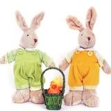 Um par de lebres macias do brinquedo bonito e de uma cesta dos ovos da páscoa fotos de stock
